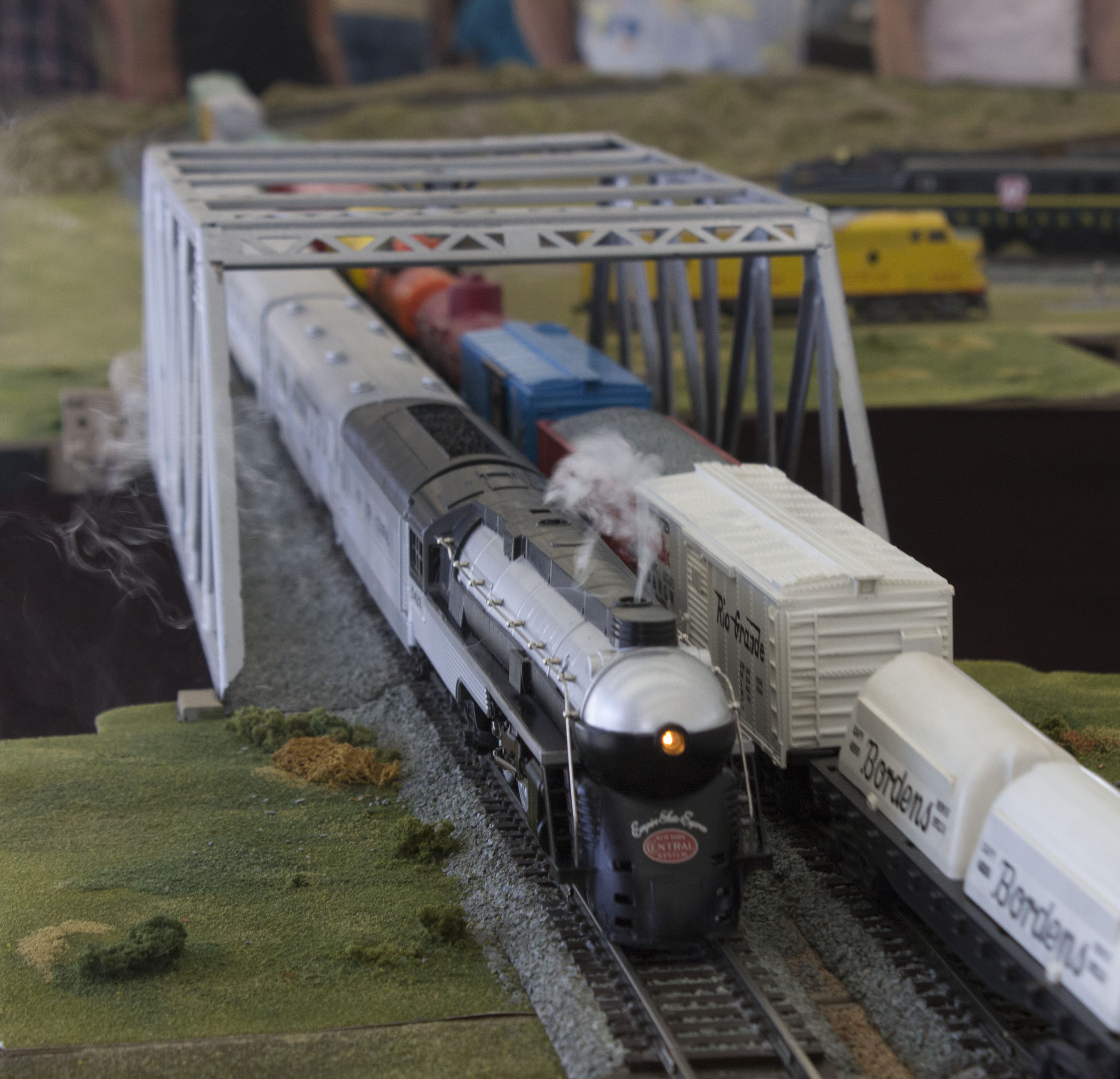 Two trains going in opposite directions meet at a bridge.
