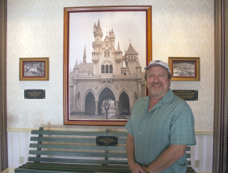Scott Zone, the official archivist of the Disney family home movies, stands in front of a bench from Griffith Park at Disneyland.