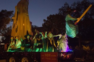 A bewitched crew being dragged along with the flying witch on a broom in the 2014 Anaheim Halloween Parade.