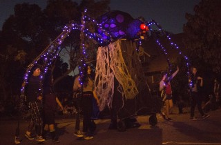 It takes eight people to keep this spider under control, one for each leg, at the 2014 Anaheim Halloween Parade.